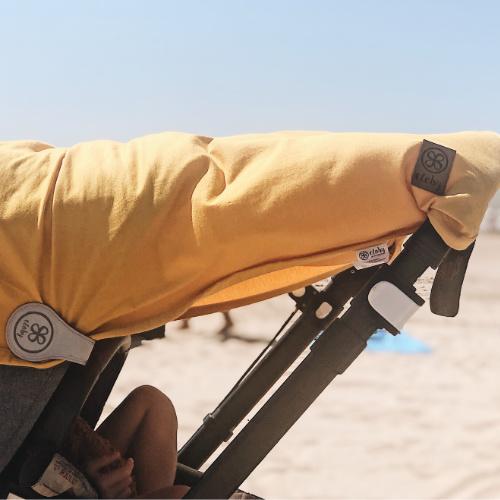 gelbe Cloby UV-Schutzdecke mit Magnetclip als Sonnenschutz für den Kinderwagen